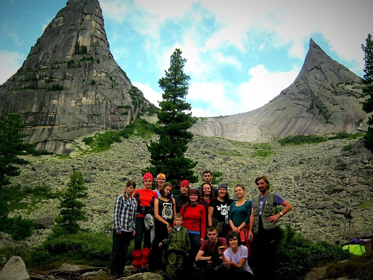 Группа туристов на фоне двух скалистых гор