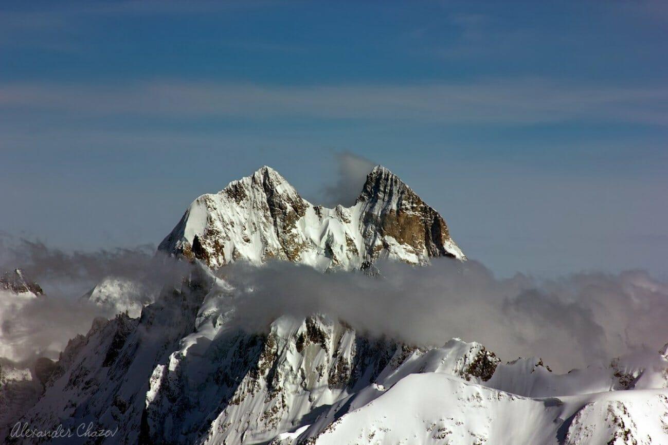 Снег и высокие горные пики в облаках
