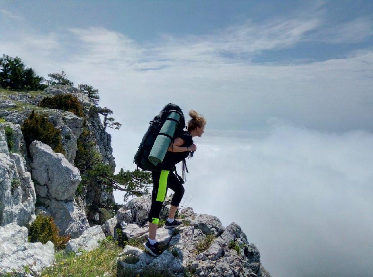 На вершине горы перед облачной долиной над обрывом