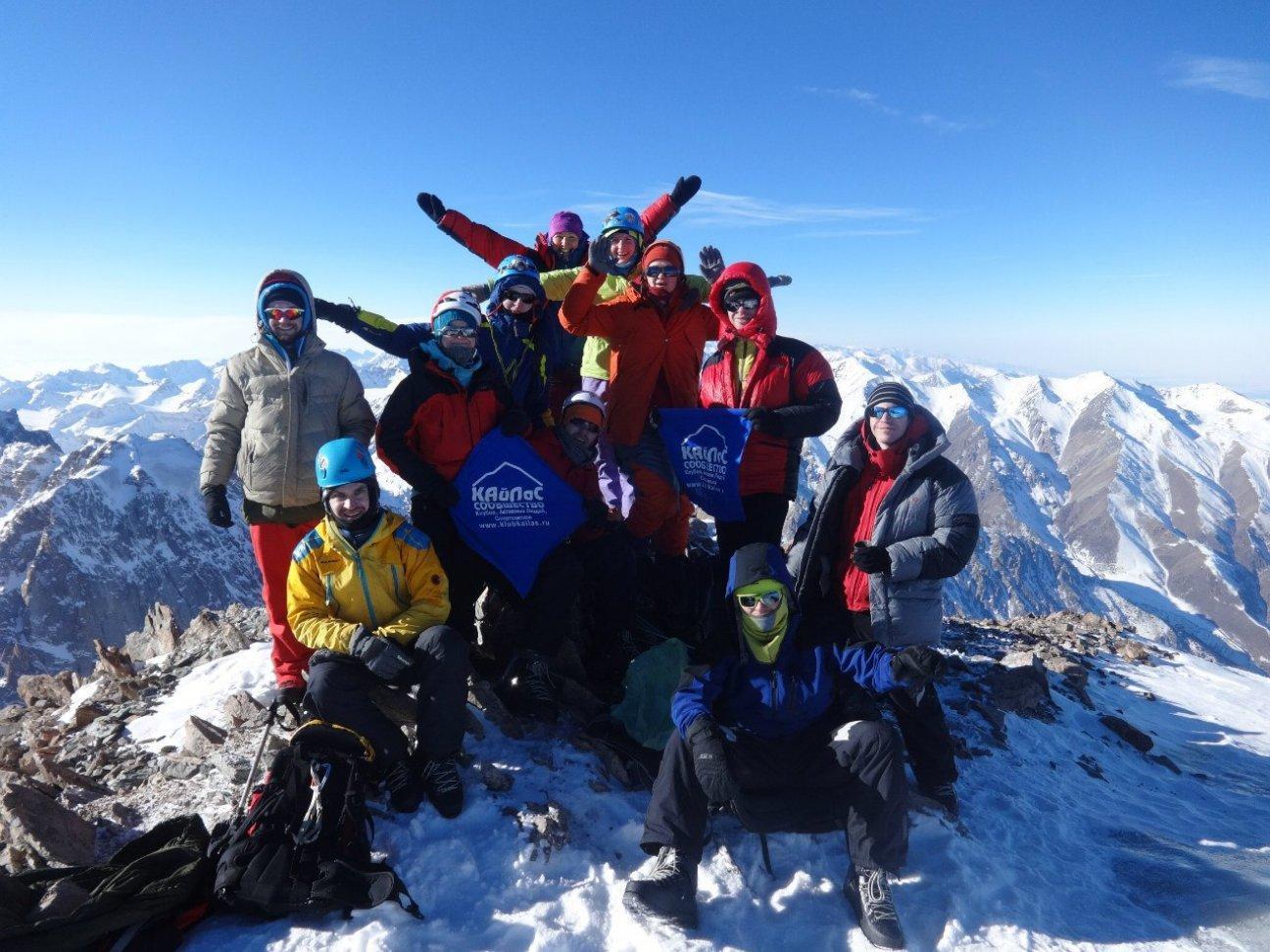 Группа альпинистов высоко на вершине горы