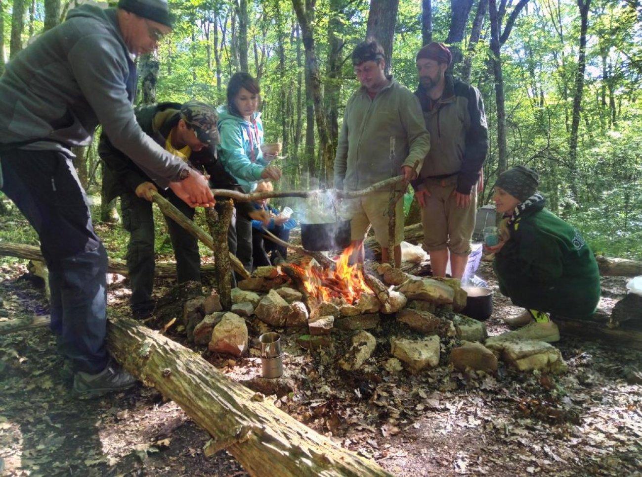 Туристы перед костром готовят обед