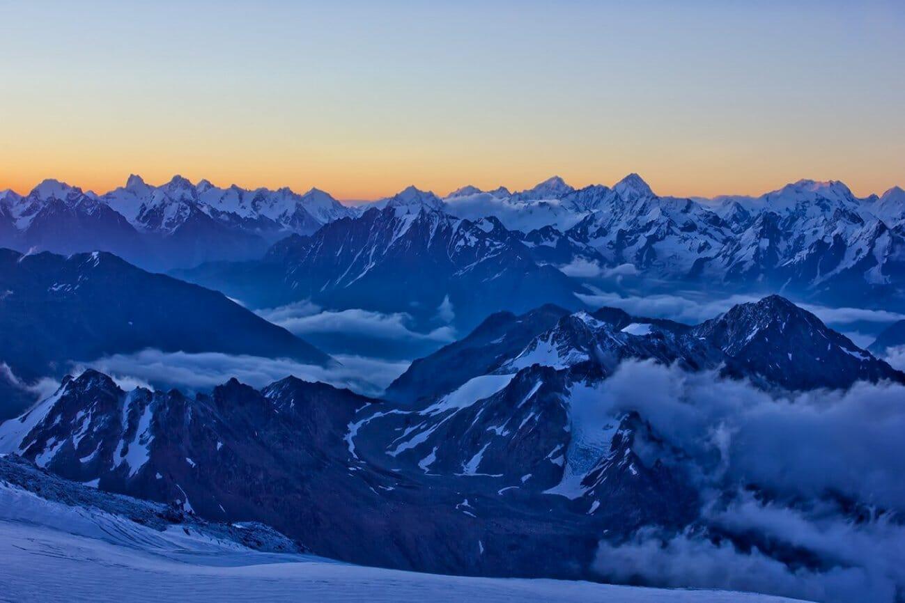 Высокие заснеженные горы в долине