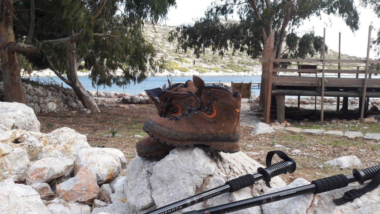 Ботинки и треккинговые палки на камнях
