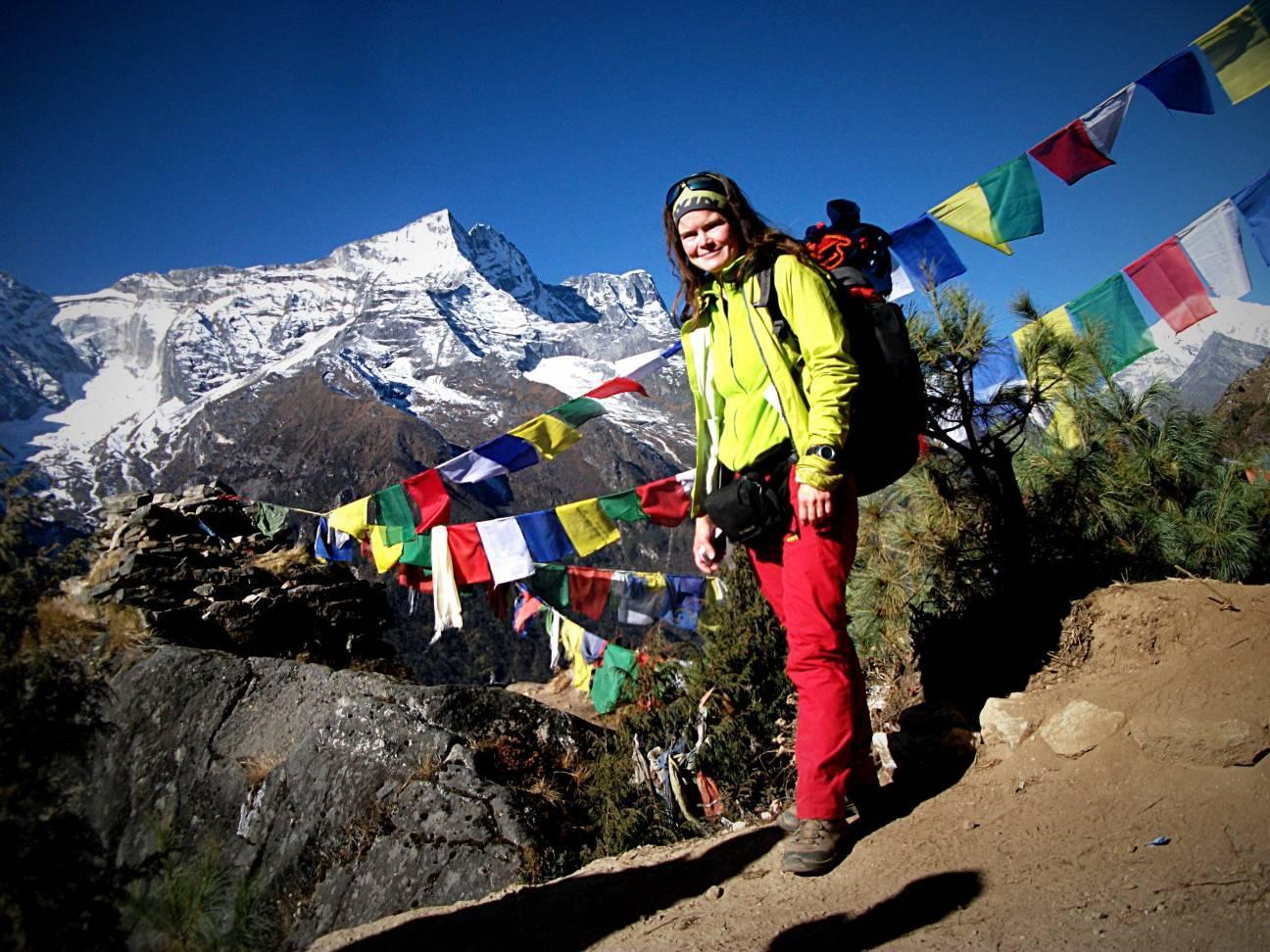 Девушка с рюкзаком на фоне заснеженных высоких гор и рядом разноцветные буддийские флажки