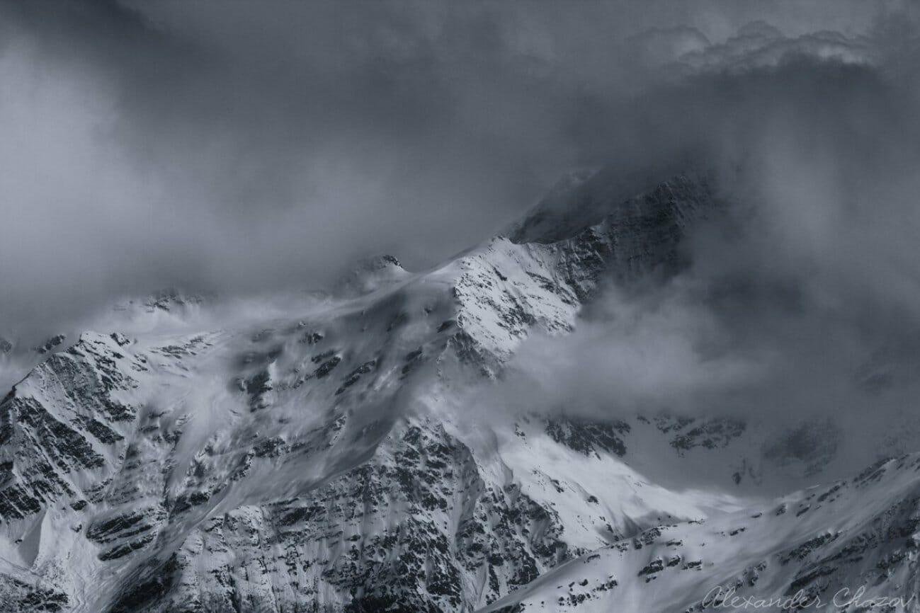 Одинокая снежная гора в облаках