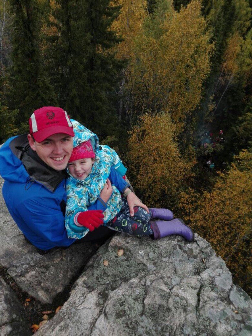 С дочкой высоко у обрыва на скале в турпоходе