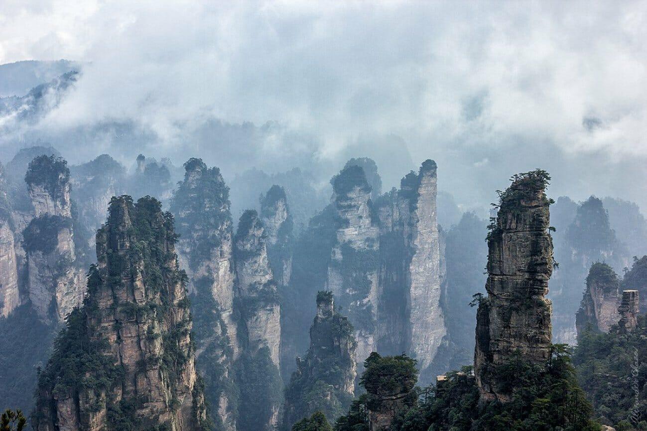 Одинокие скалы в долине в джунглях в облаках