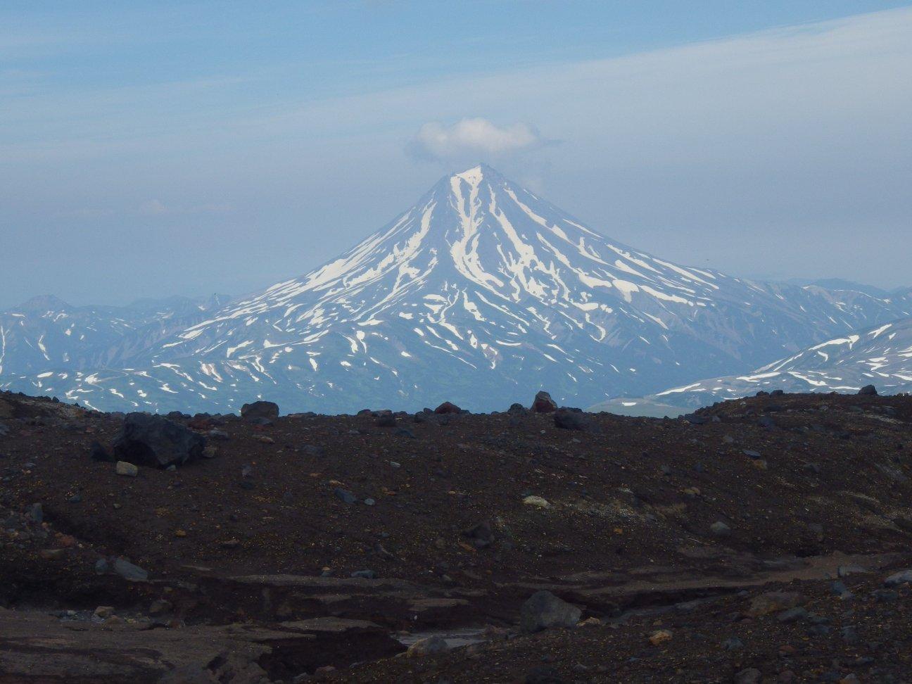 Высокая снежная гора на фоне степи