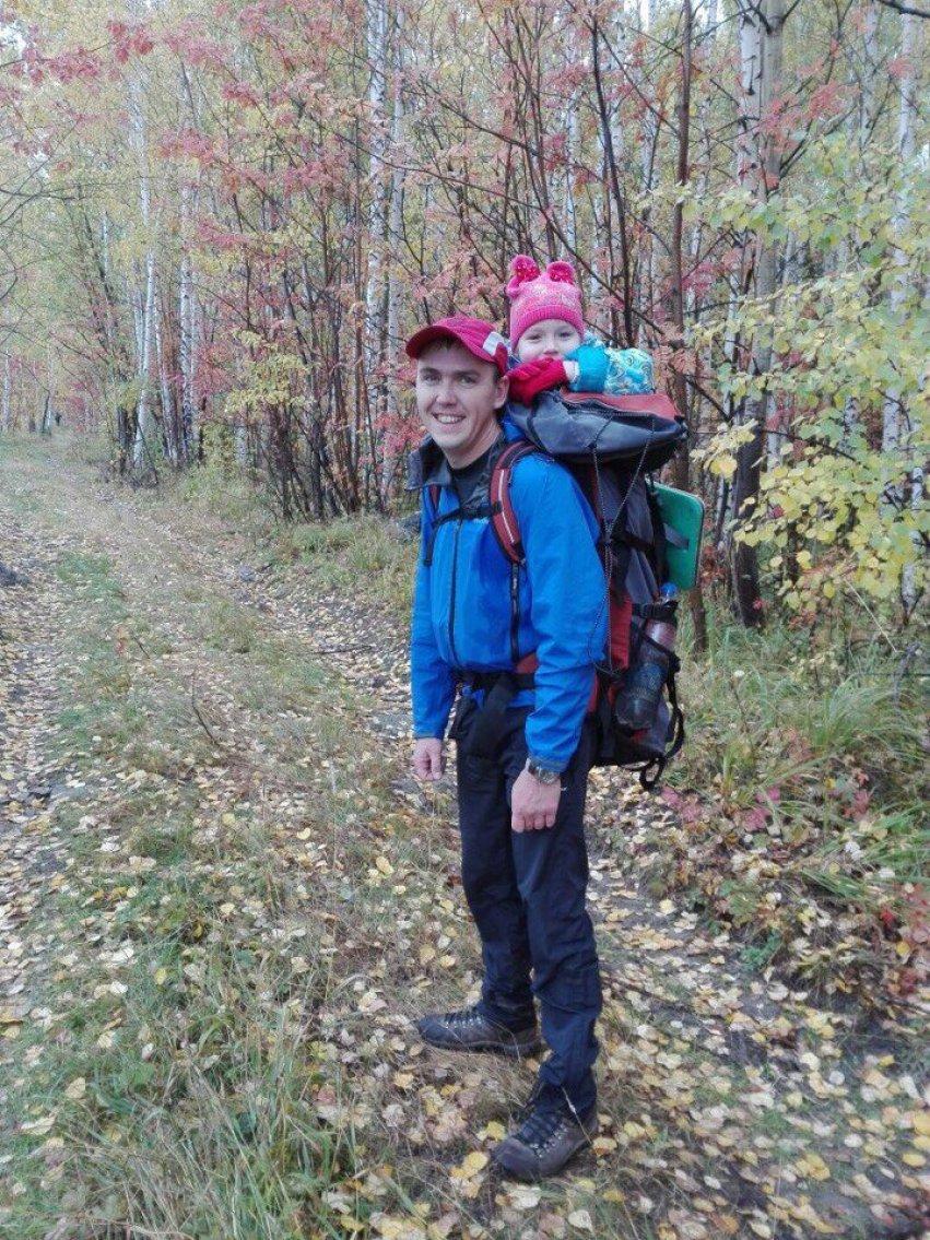 С дочкой на рюкзаке в лесу в туристическом походе