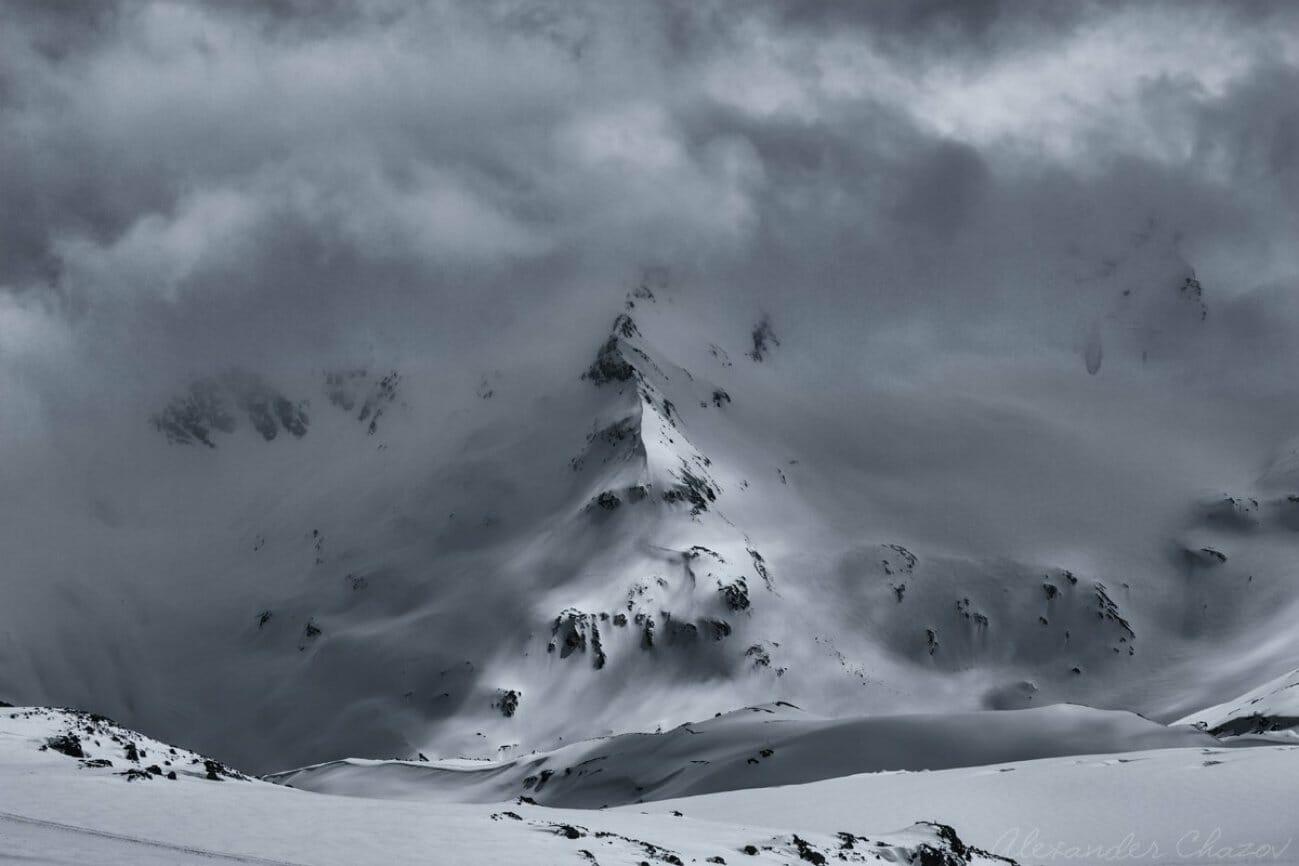 Заснеженная гора вся в тумане и облаках