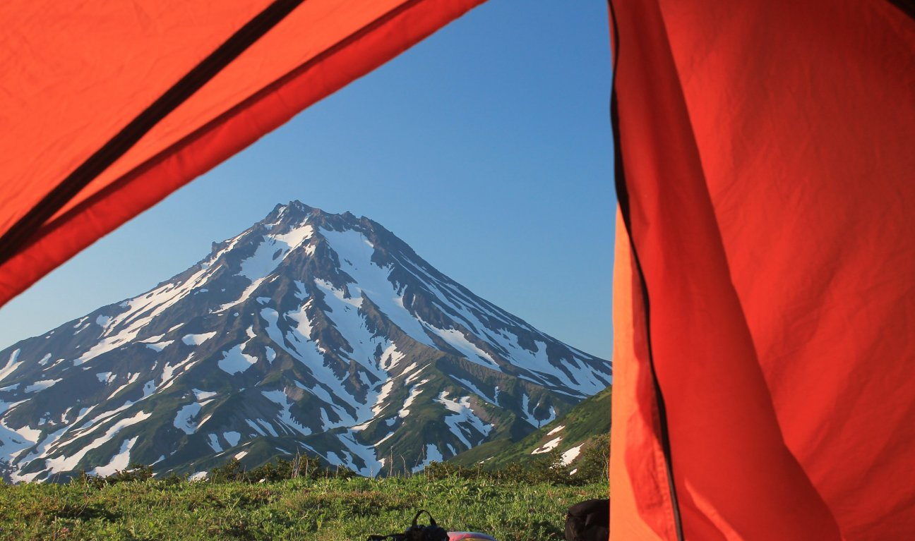 Великолепный вид на снежную гору из палатки