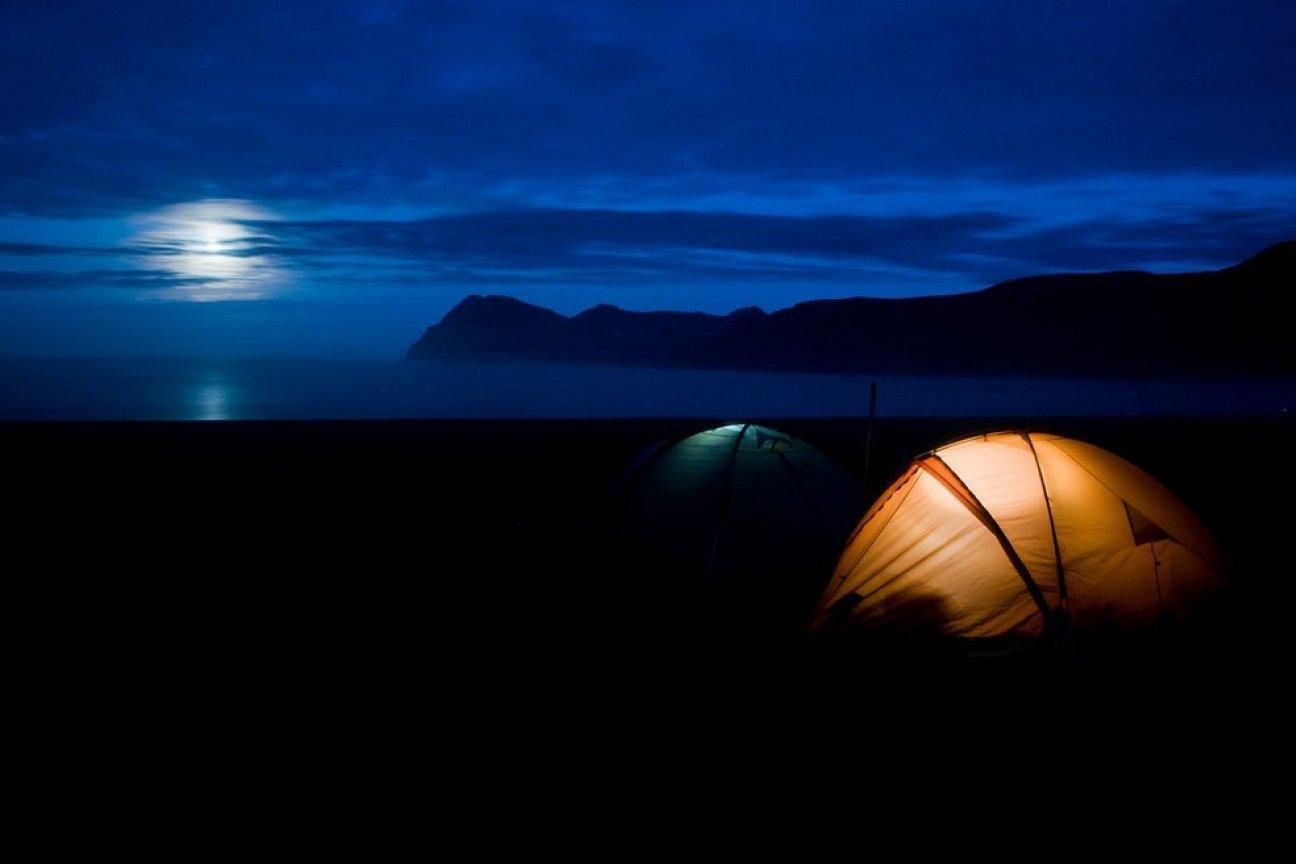 Палатки в ночи в снежных горах