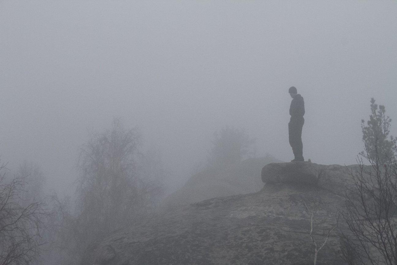 Одинокий турист в тумане на скале