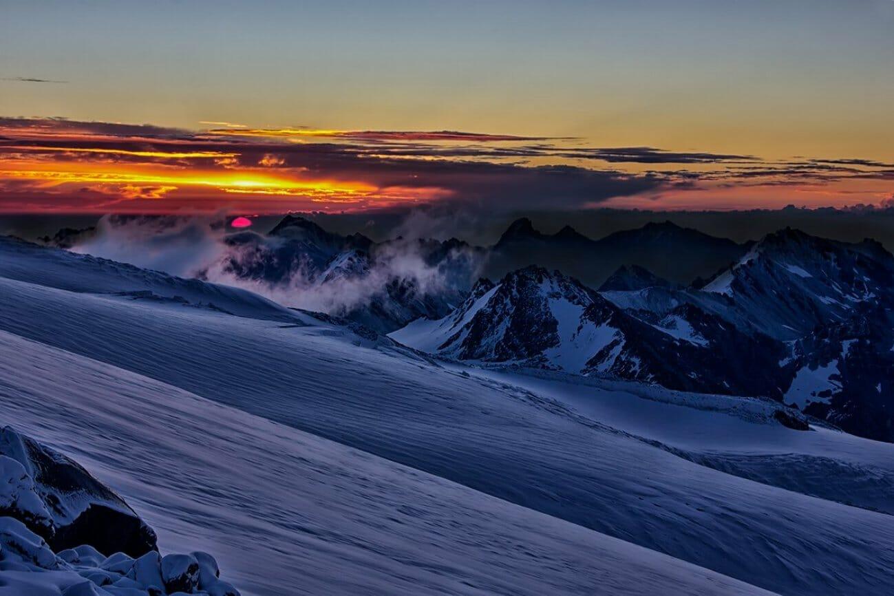 Яркий закат высоко в снежных горах