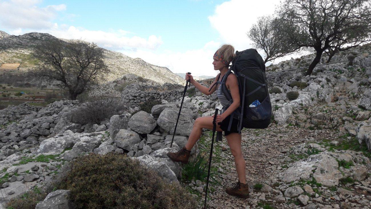 В горах с треккинговыми палками и большим рюкзаком