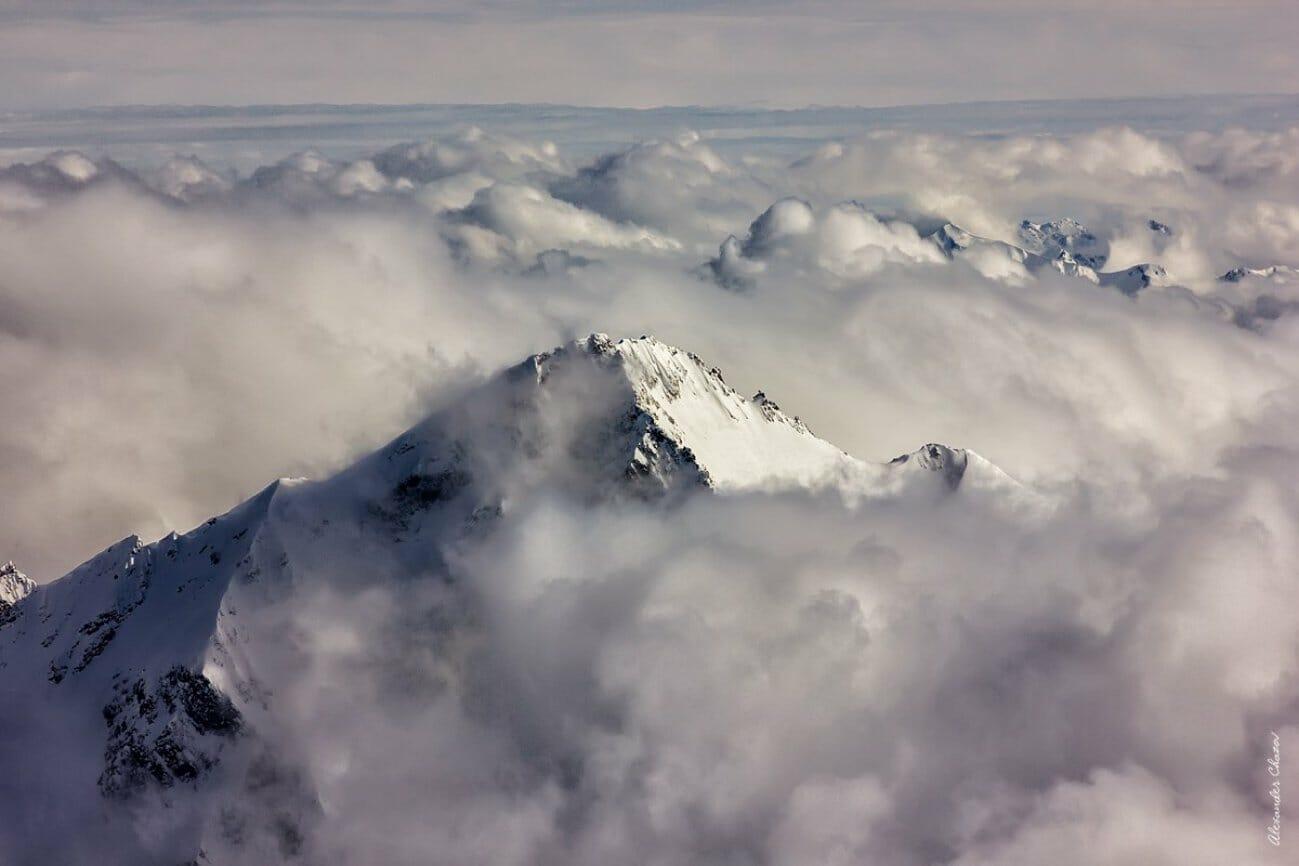 Вершина горы над облаками в снегу