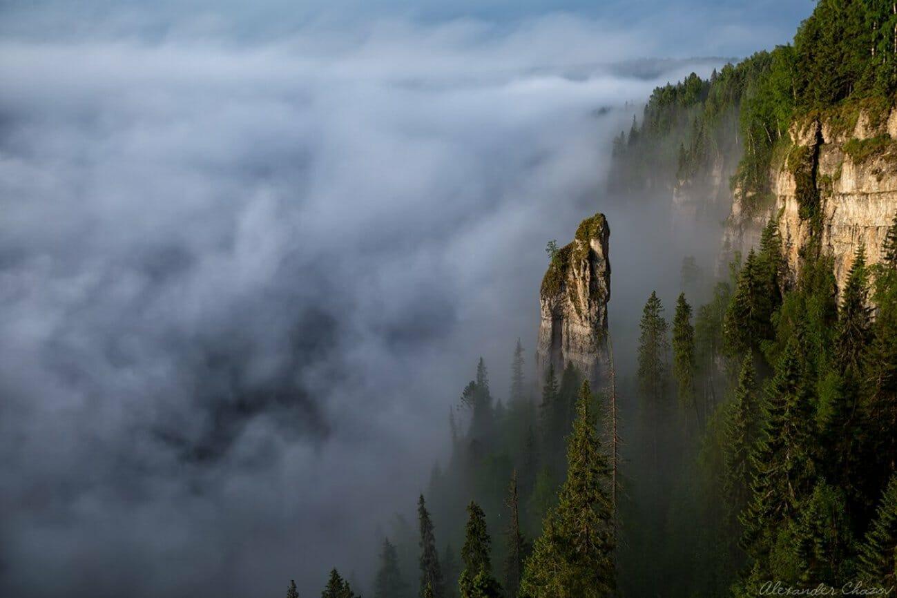 Одинокая скала в тумане над облаками