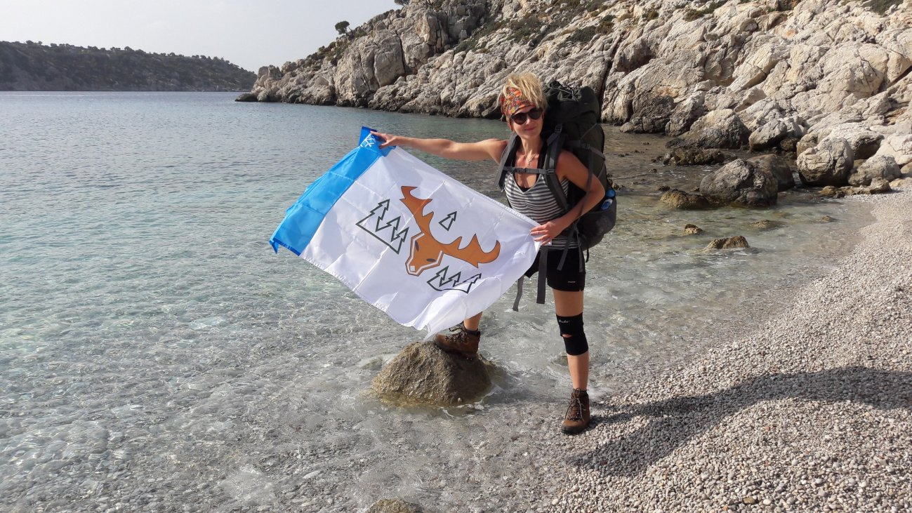 С флагом Лабытнанги на фоне моря и скал