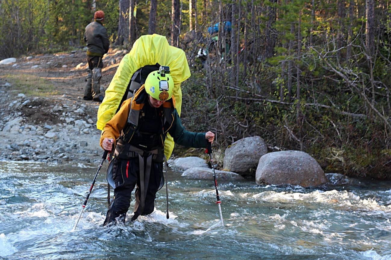 Девушка с большим рюкзаком и палками переходит реку