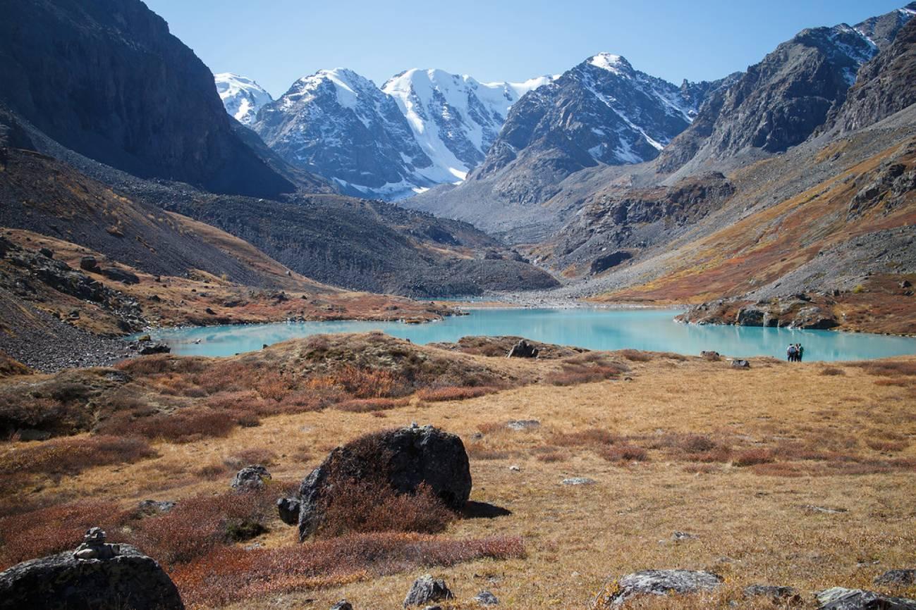 Высокие горы и туристы возле горного озера