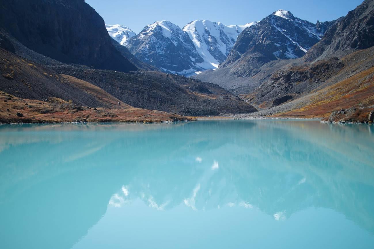 Голубое высокогорное озеро на фоне заснеженных горных пиков