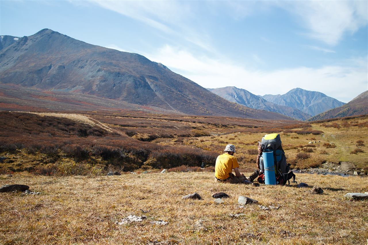 Путешественники отдыхают на равнине в горах Алтая
