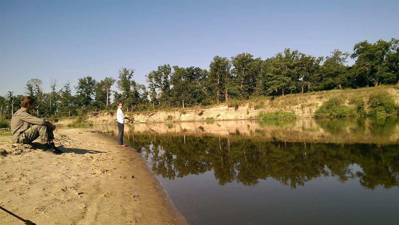 Девушка рыбачит на реке
