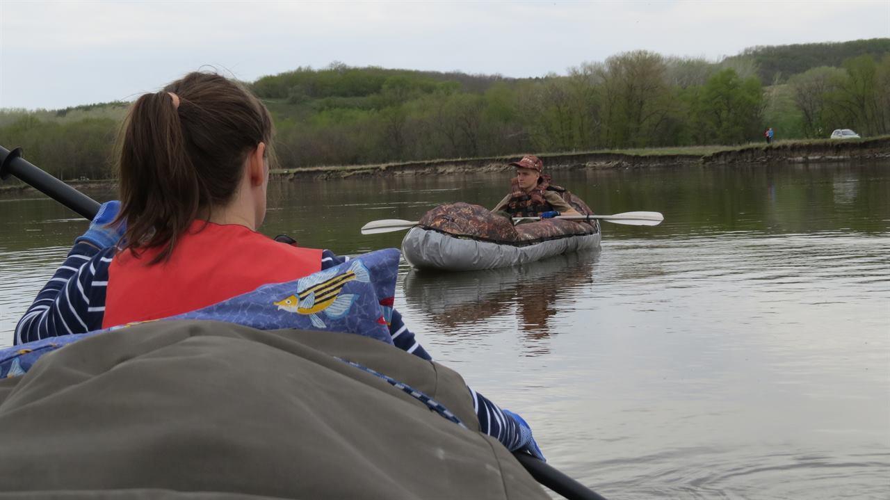 Мужчина и девушка в лодках на реке