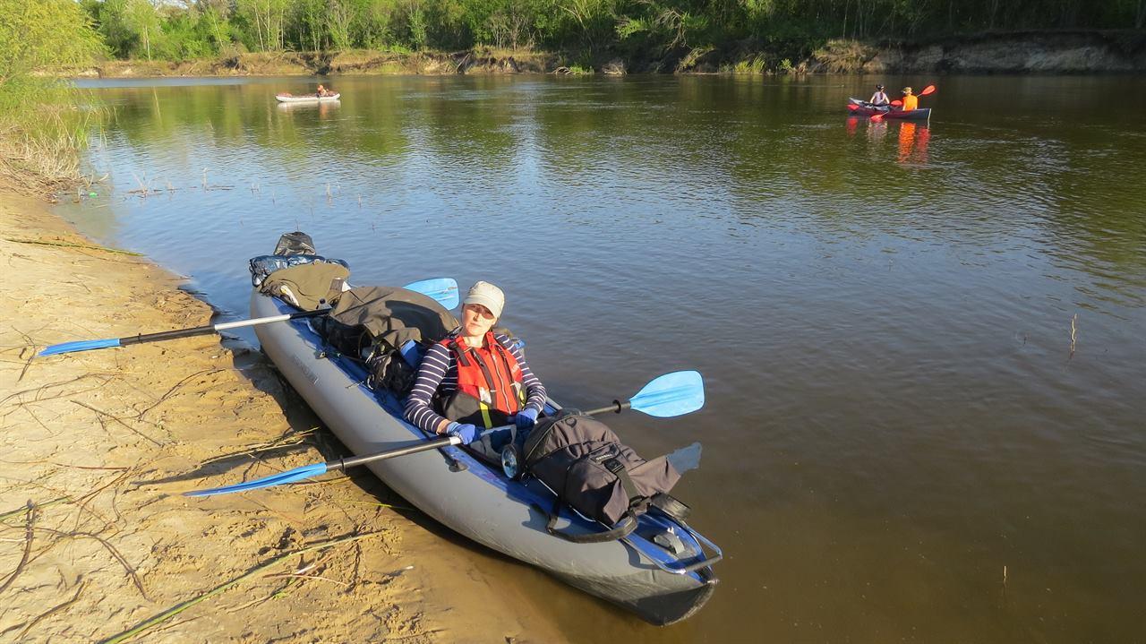 Девушка на берегу реки в надувной лодке на сплаве