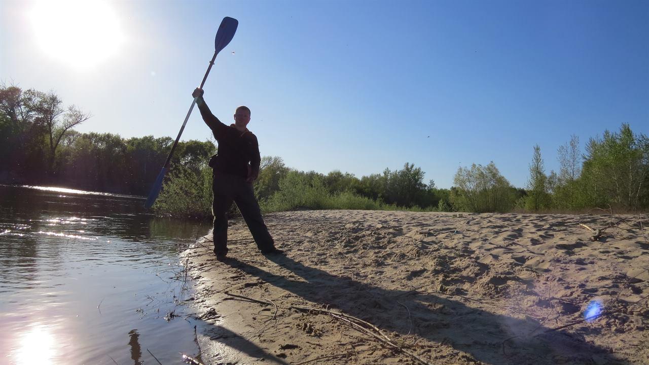Путешественник с веслом в руках на сплаве