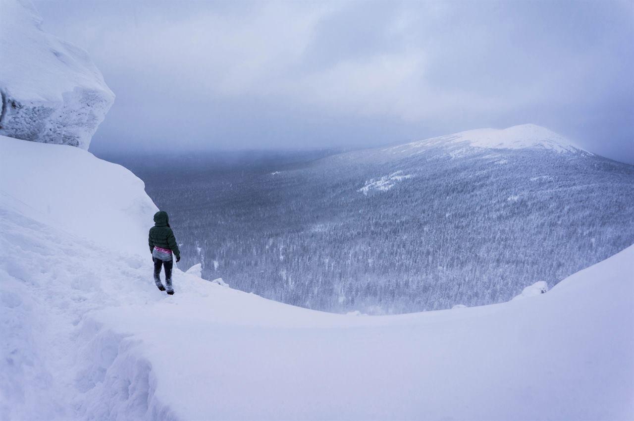 На краю снежного обрыва в горах