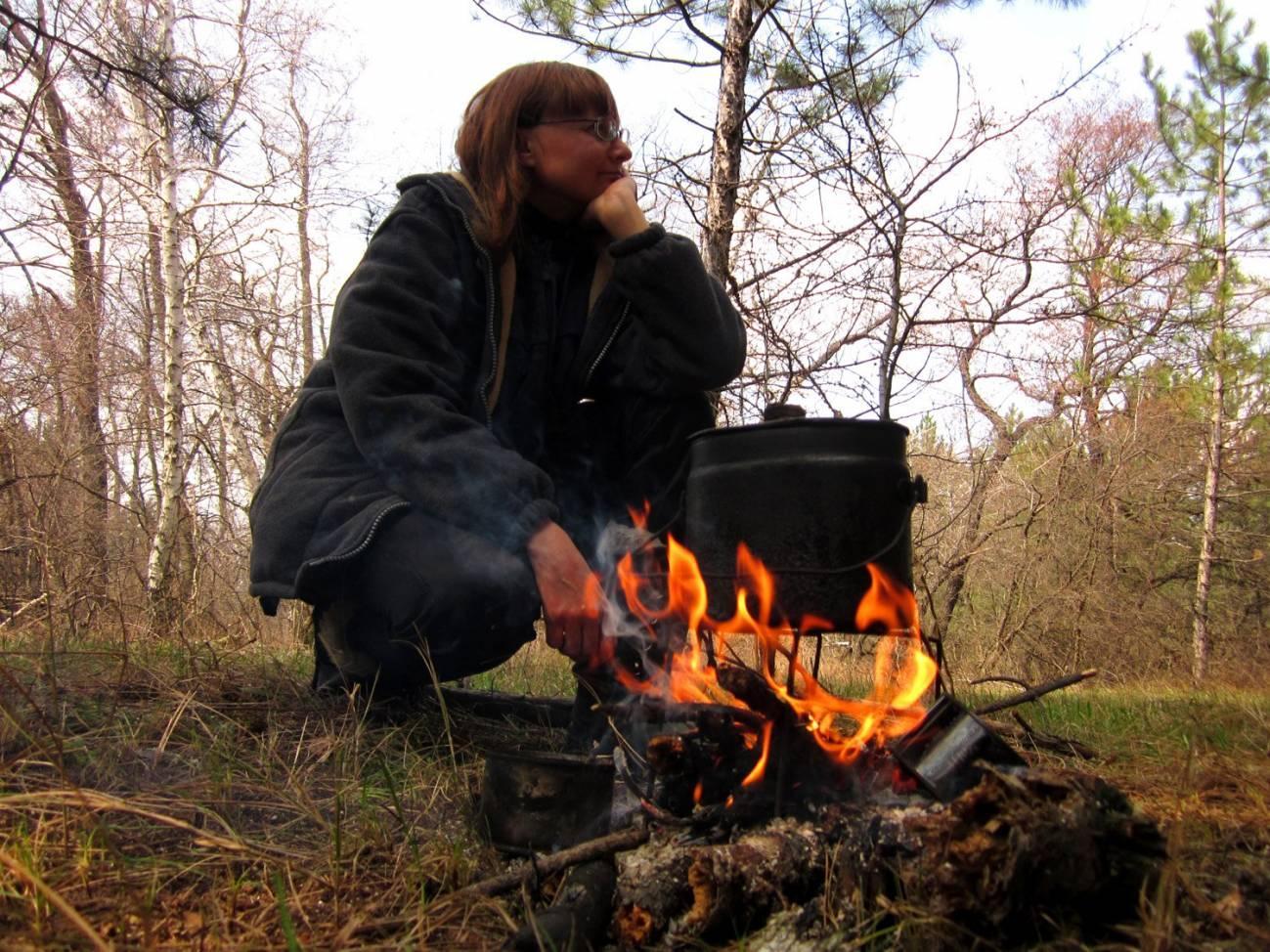 Путешественница возле костра готовит пищу
