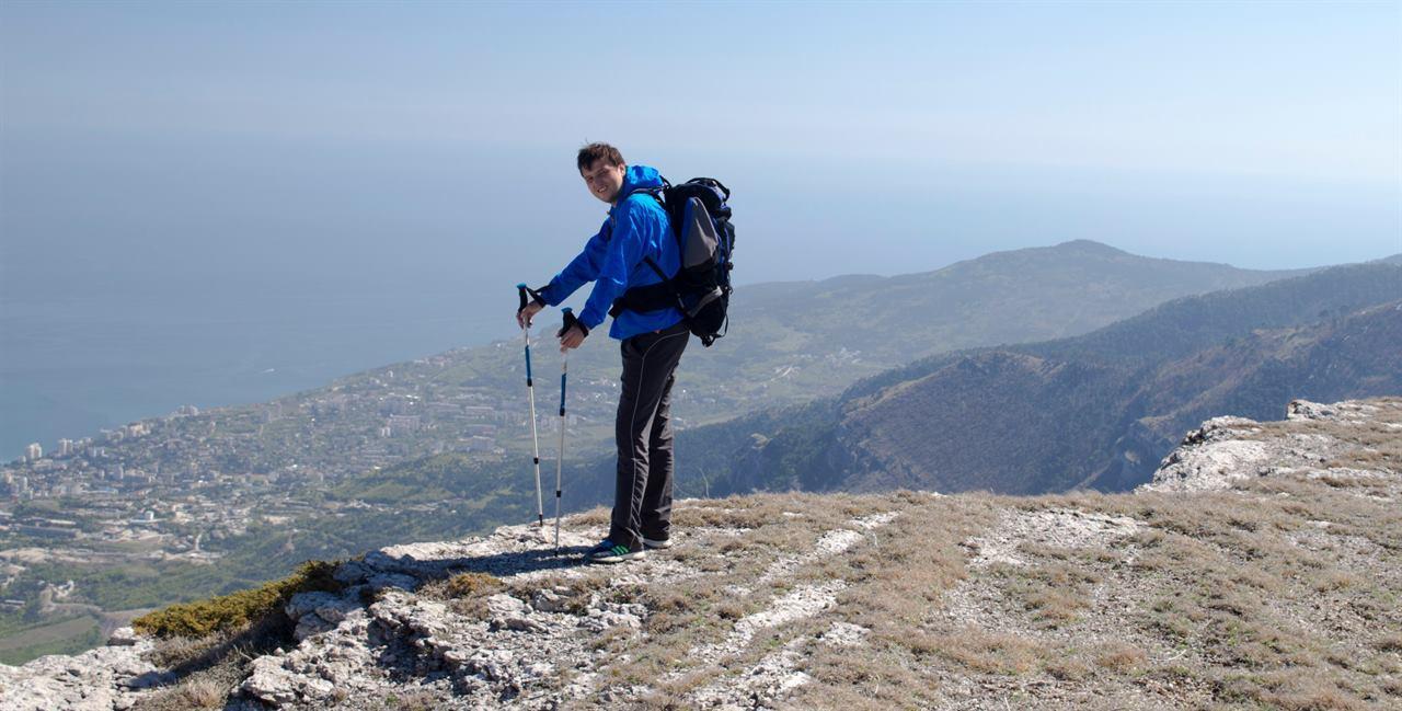 Путешественник в горах на фоне долины