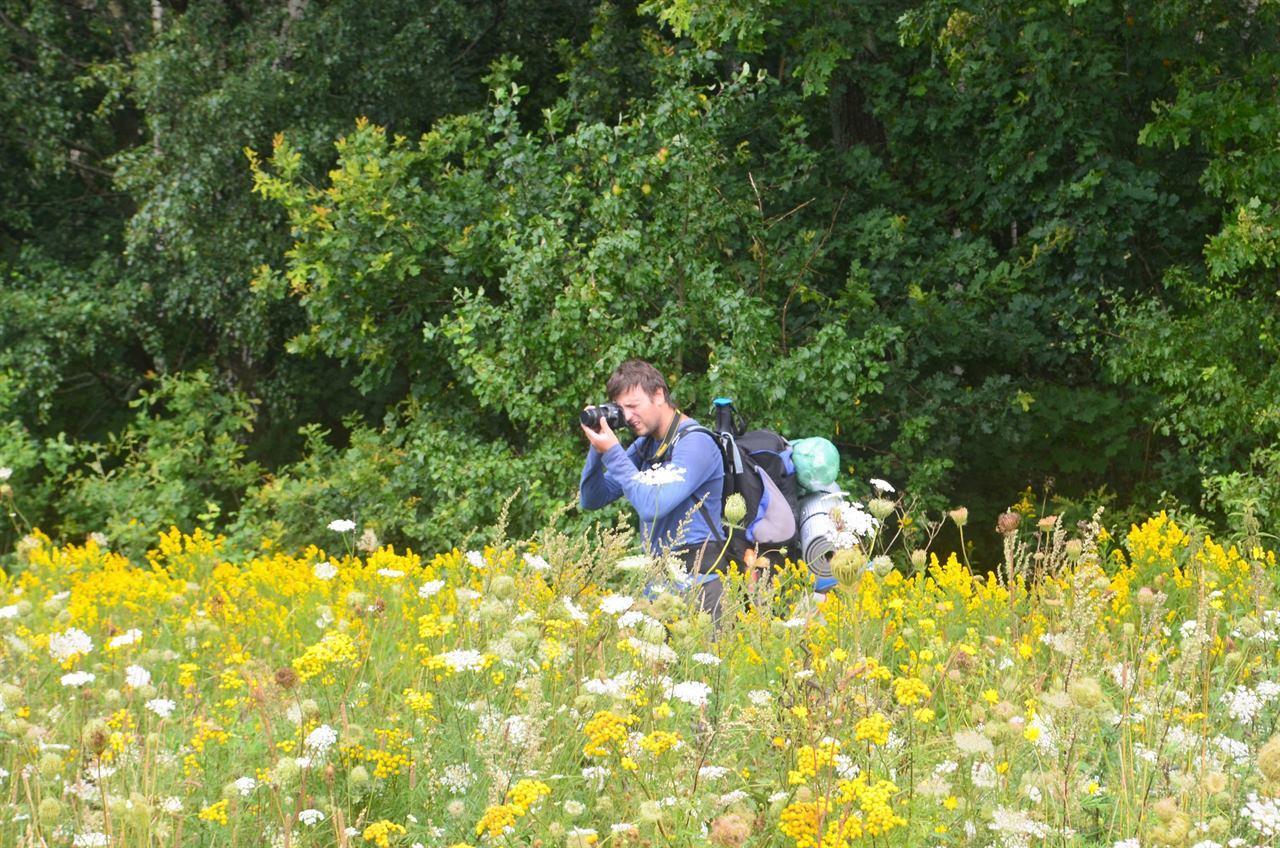 Фотограф в походе с фотокамерой ведет съемку