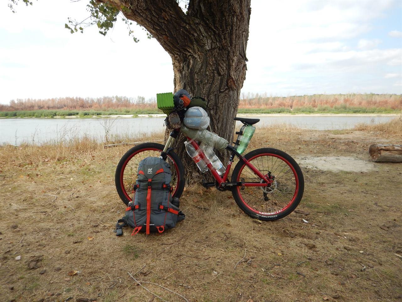 Велосипед у дерева с рюкзаком