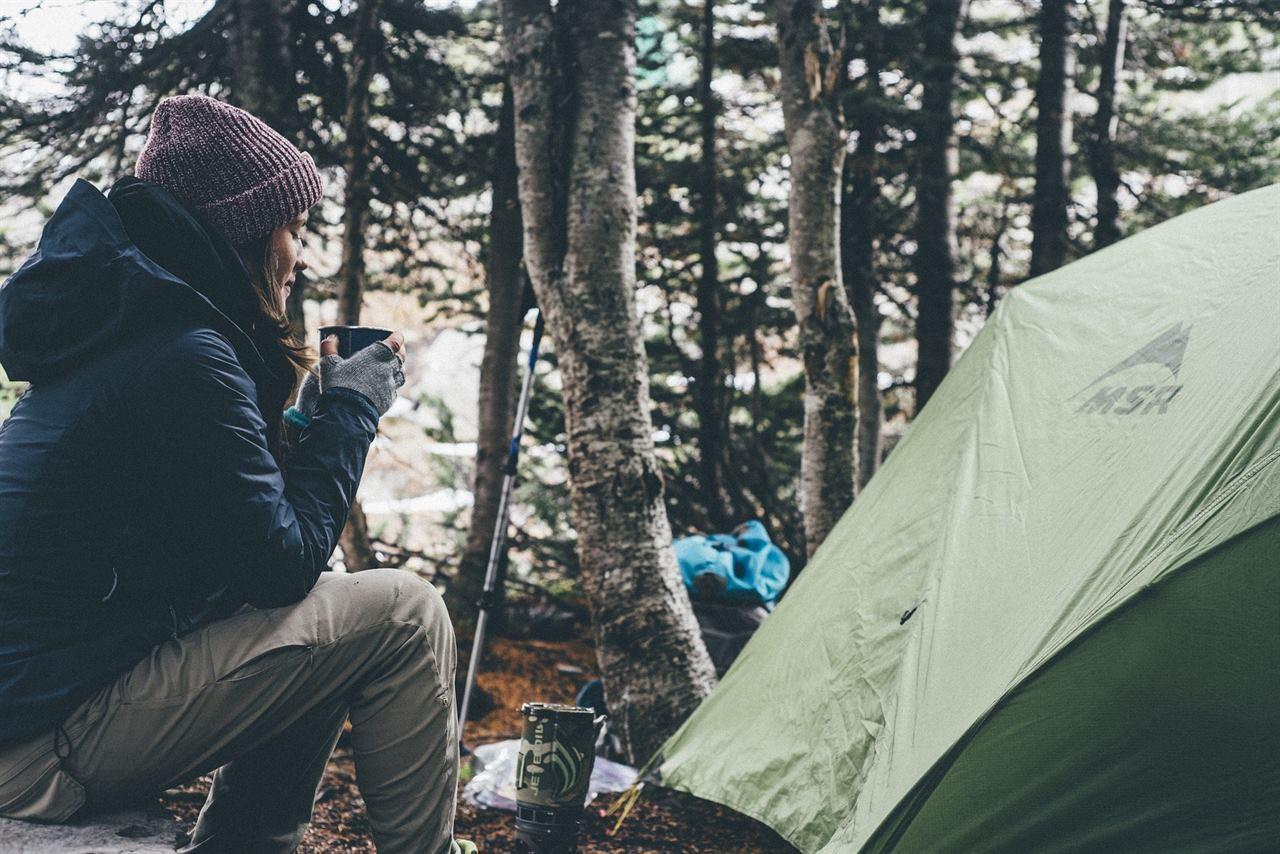 Путешественница у палатки в лесу