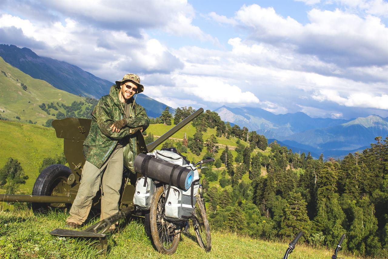 В горах на велосипеде рядом с пушкой