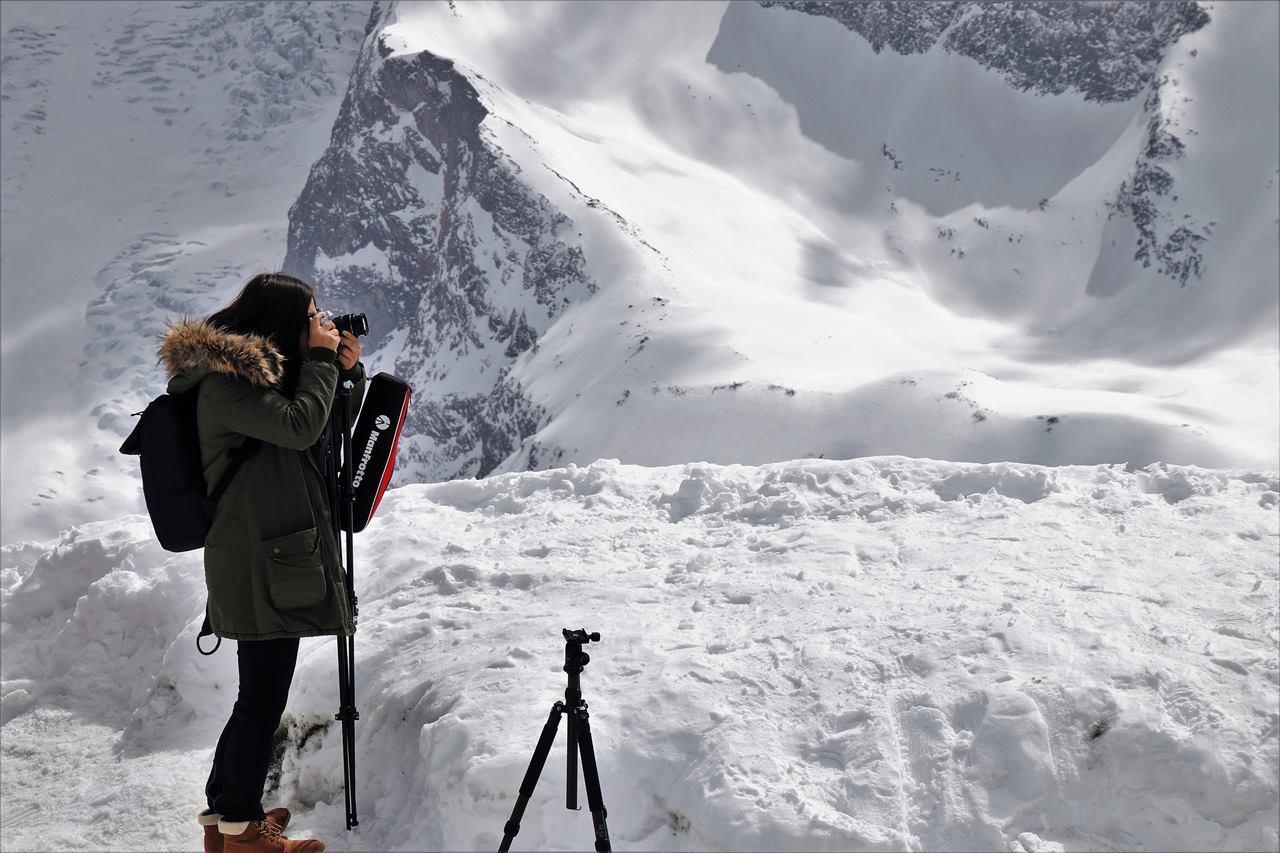Девушка фотографирует природу зимой в горах