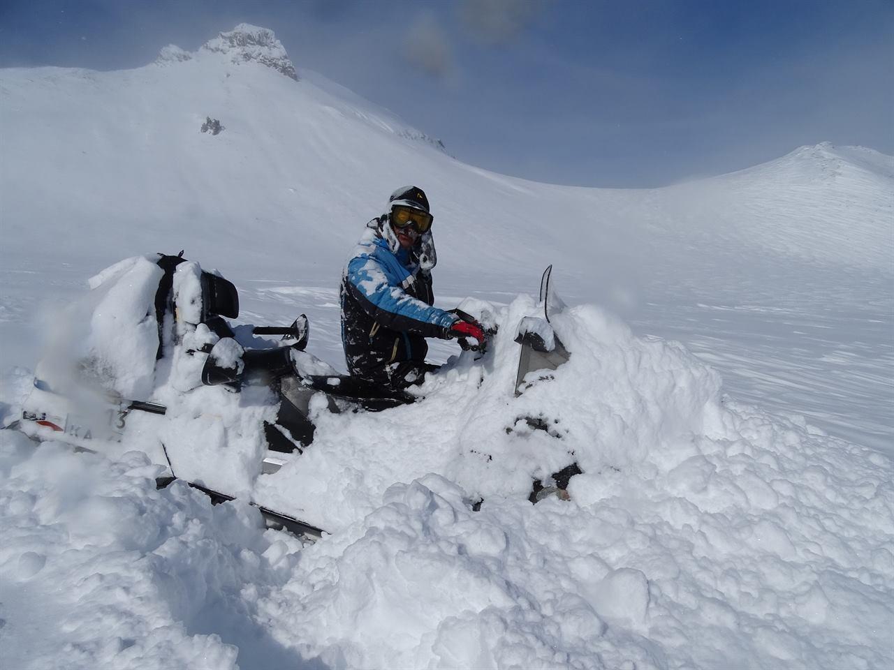 Путешественник в снегу на снегоходе