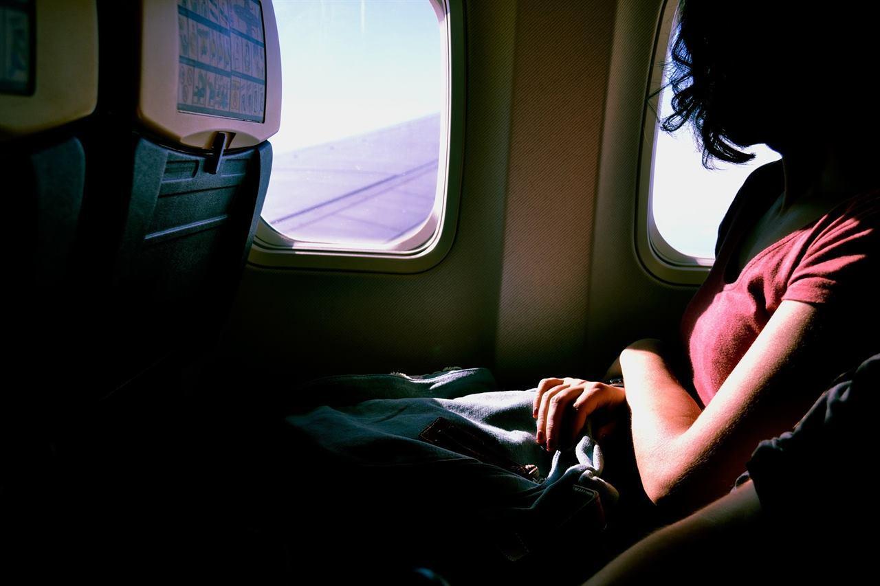 Путешественница перед эллюминатором самолета