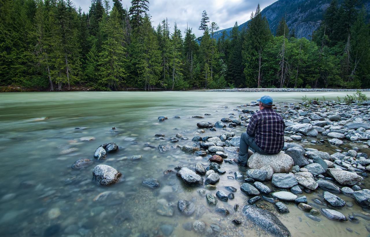 Путешественник отдыхает на камнях у реки