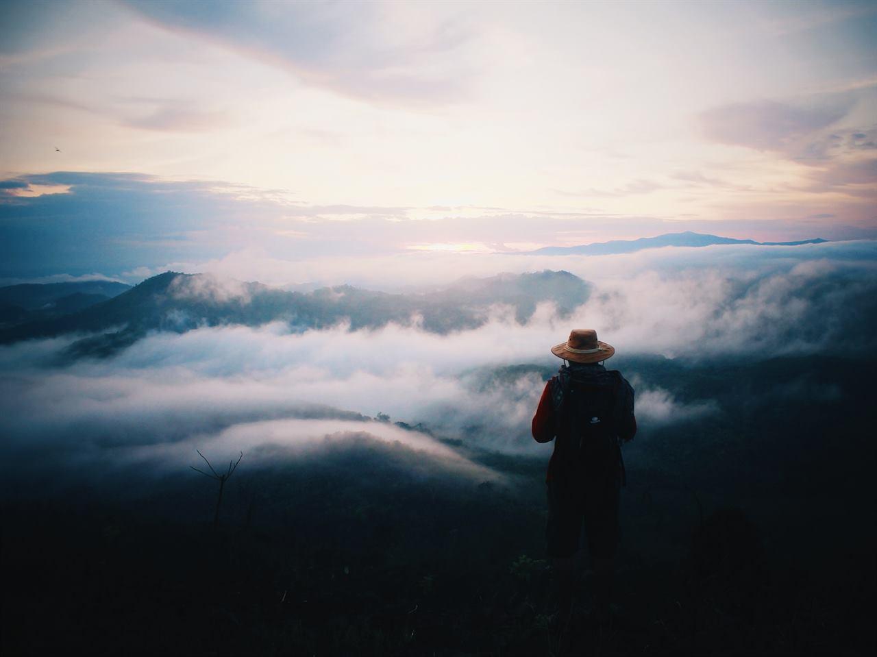 Путешественник над облаками в горах