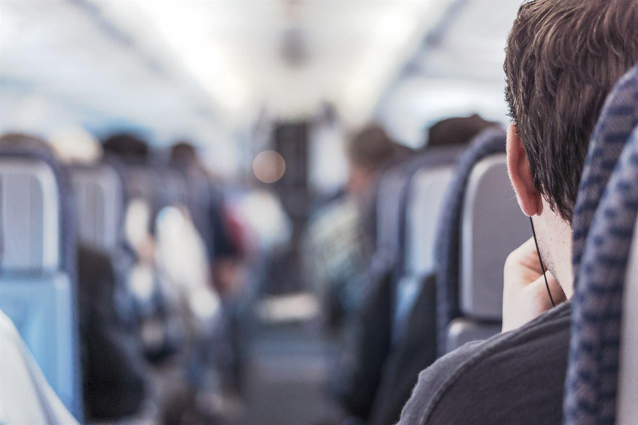 Турист в самолете в наушниках