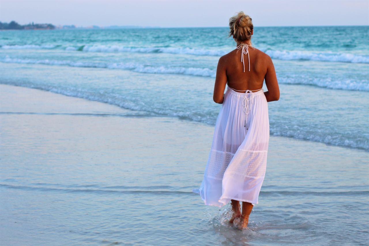 Туристический пляж с женщиной на песке