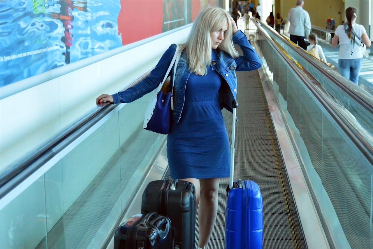 Девушка в аэропорту с чемоданами путешествует